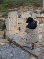 A visitor taking photos in the ruins of Ephesus Ancient City.